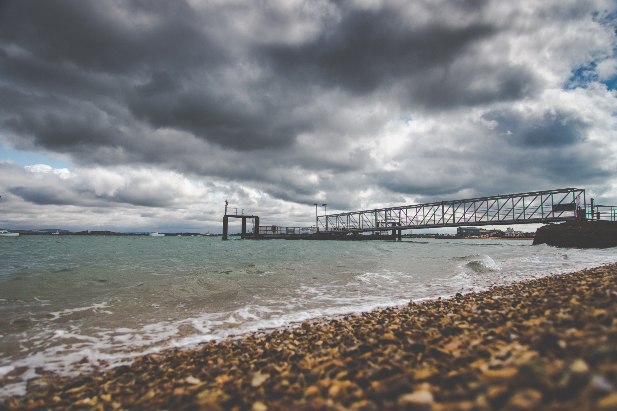 View of the Hayling Ferry from the Eastney Beach, with a rising tide and a cloudy sky