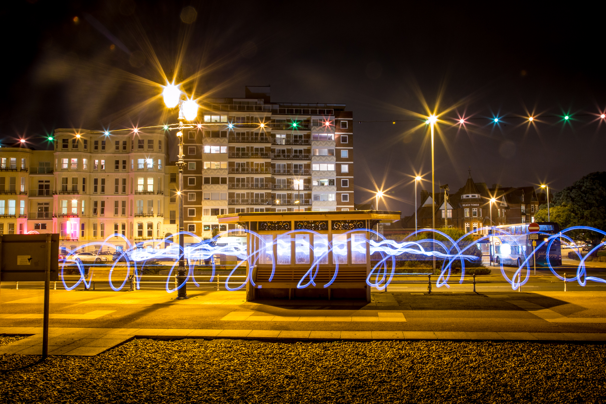 Colourful light painting in front of a Southsea yellow shelter at night.
